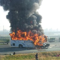 A tour bus enveloped in flames after rear-ending a container truck on an expressway near Beijing on Oct 1, 2012. [Photo from weibo.com/lifecuc]
